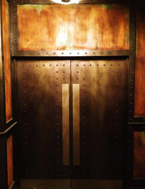 The rusted walls compliment the bronze and gold paint effect to the doors which were eventually studded to portray a metallic finish to the nightclub design.