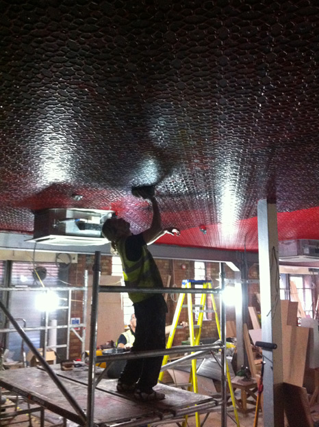Working on the Lincrusta ceiling with pillar box red, distressed decorative paint finish, at The Harp Bar Belfast, Northern Ireland.