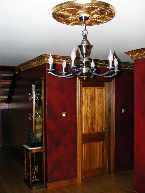 The cornice and ceiling rose was gilded in dutch metal gold leaf. It was gilded to compliment the red leather faux finish on the walls.