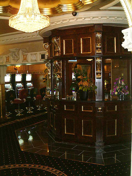 Ornamental kiosk with walnut woodgrain panels adorned with gilded corbels.