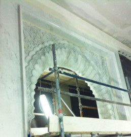 White Carrara faux marble archway with faux stone decorative moulding.
