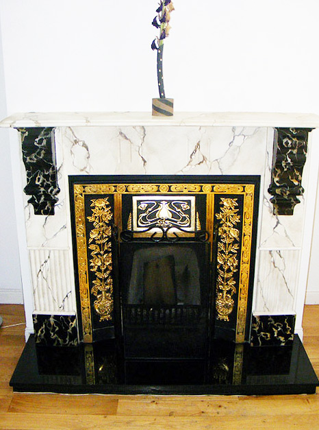 White Breche faux marble fireplace and mantel, with Portoro faux marble corbels. The decorative fire surround was gilded with gold leaf.