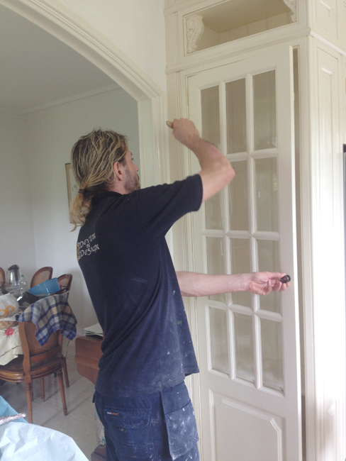 Our decorative painter applying the glaze ready for antiquing and aging the kitchen surface. The ageing process required on this particular surface was ever so slight as the overall design requires a light aged paint finish.