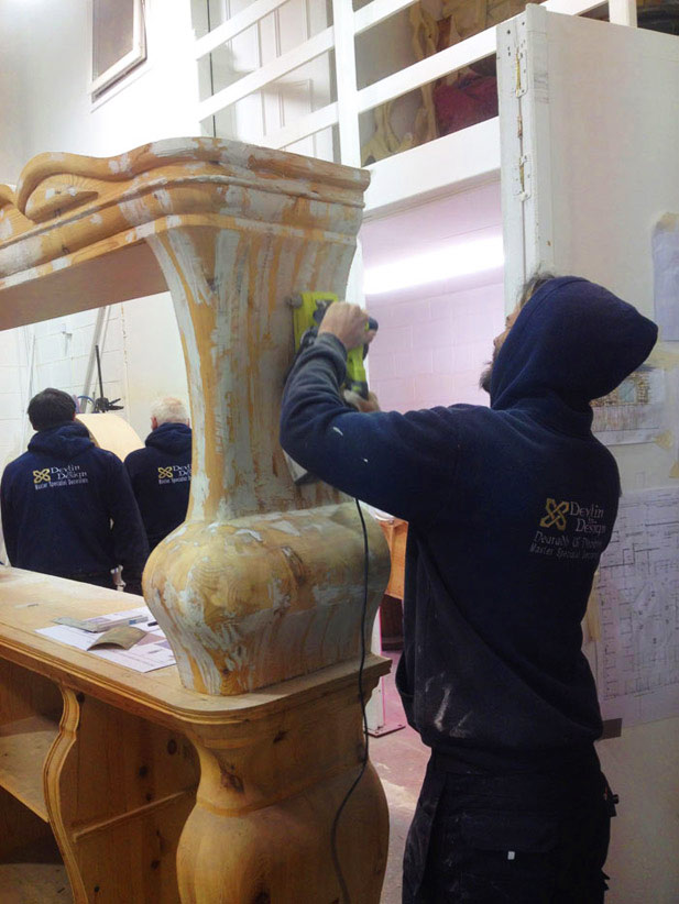Decorative paint finish specialists preparing the boxed gothic wine rack for mosaic and ornamental painting.