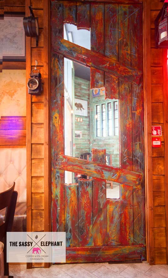 Heavily distressed wooden door with aged surround, created and hand painted by Devlin in Design artists and craftsmen.