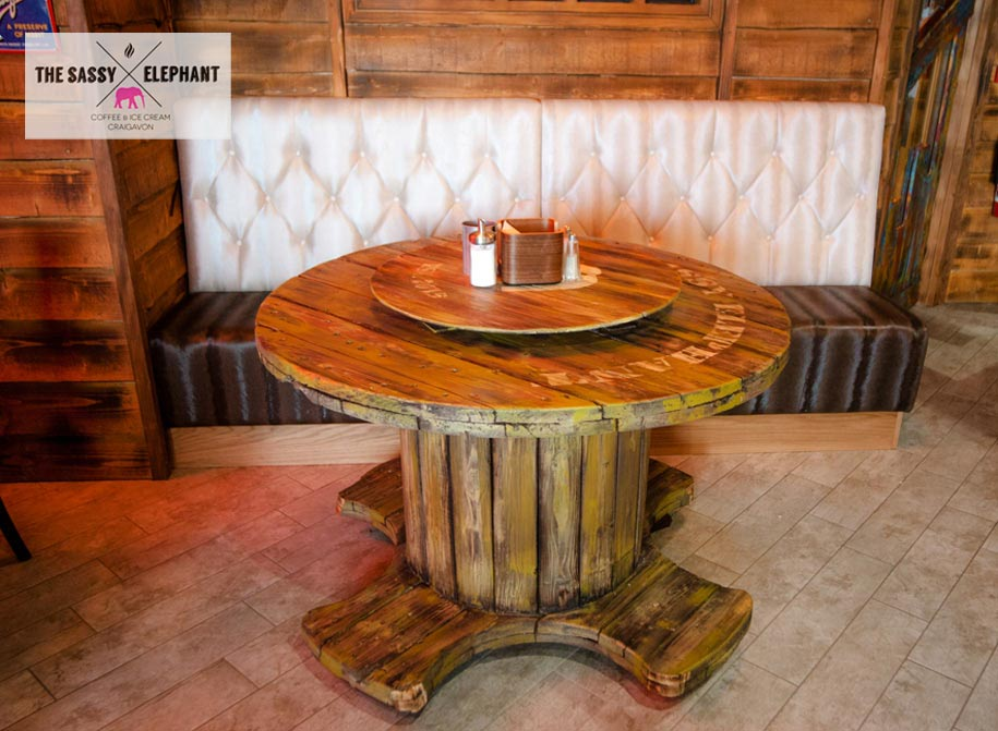 Hand painted table, created with distressed and aged wood and branded with The Sassy Elephant logo. One of a range of wooden tables designed and created by Devlin in Design specialist decorators.