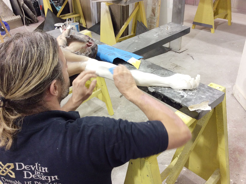 Moulding and restoring the missing arm of Saint Mother Teresa's crucifix.