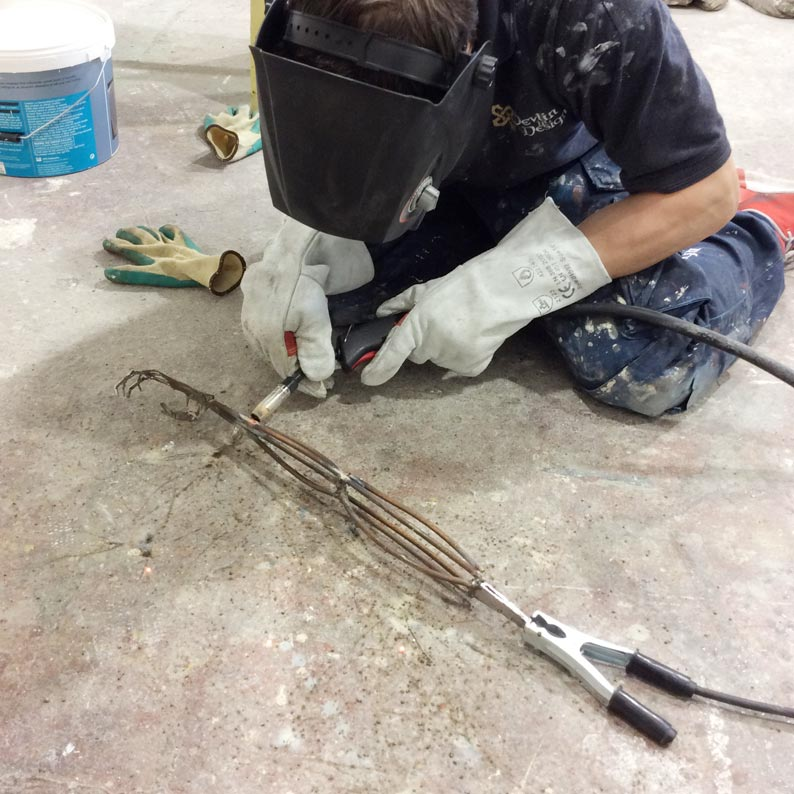 Welding the detailed arm to Saint Mother Teresa's crucifix