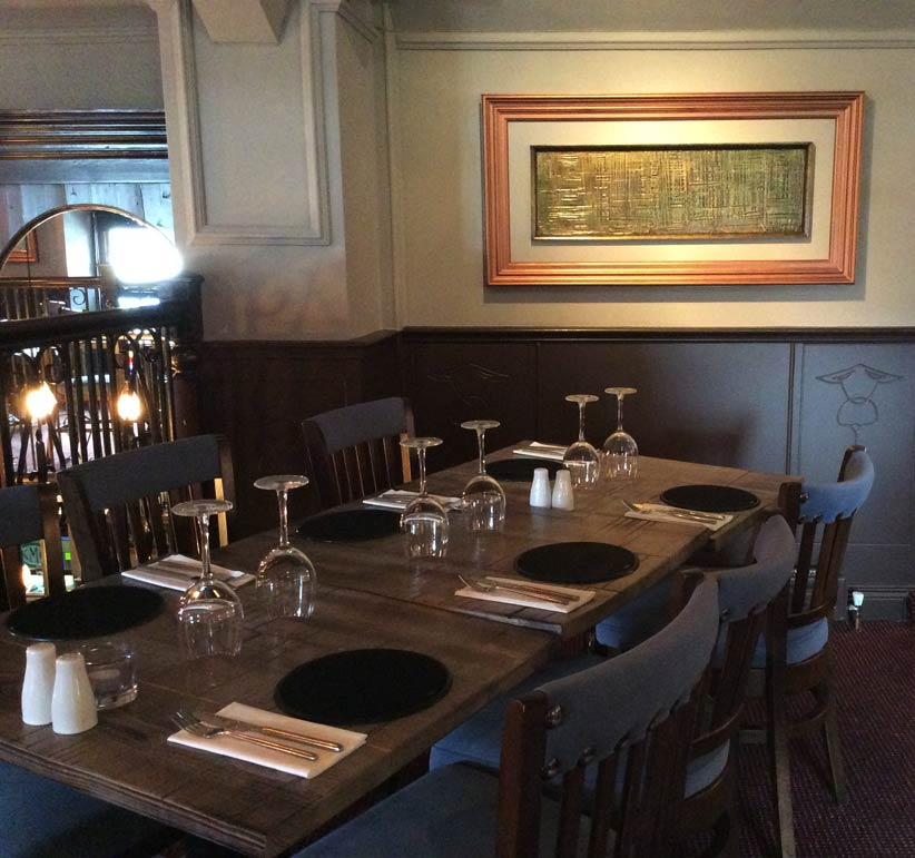 Copper and brass antique framework with restaurant artwork and distressed restaurant tables manufactured by Devlin In Design.