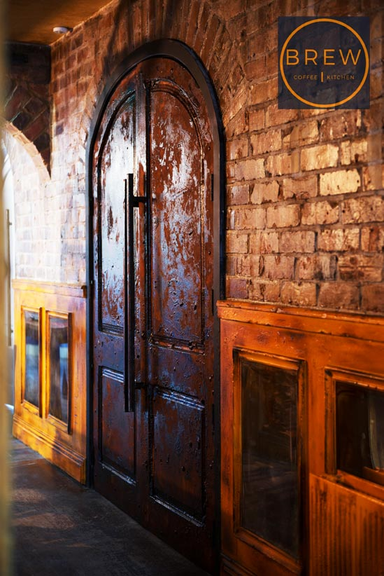 Rust arched doorway, with decorative rust wall panels and aged brick walls for restaurant interior, Northern Ireland.
